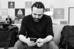 Knappe jonge mens met dreadlocks die zijn telefoon met behulp van bij een luchthavenzitkamer met backlight Stock Foto's