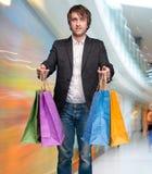 Knappe jonge mens met het winkelen zakken Royalty-vrije Stock Afbeelding