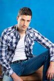 Knappe jonge mens met plaidoverhemd op blauw Stock Fotografie