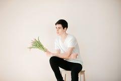 Knappe jonge mens met roze tulpen Royalty-vrije Stock Afbeelding