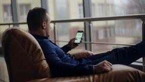 Knappe jonge mens op zijn telefoon in elegante plaats stock videobeelden