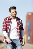 Knappe jonge mens in witte t-shirt, overhemd en jeans in openlucht Royalty-vrije Stock Afbeeldingen