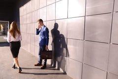 Knappe jonge mens, zakenman die op telefoonpassen door beaut spreken stock foto