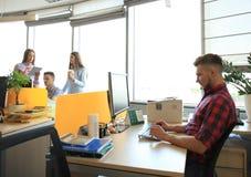 Knappe jonge mensenglazen die slimme telefoon houden en het bekijken terwijl het zitten op zijn werkende plaats stock foto