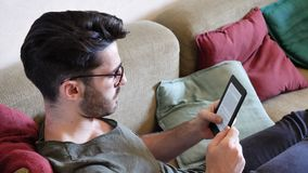 Knappe jonge mensenlezing ebook op bank stock videobeelden