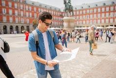 Knappe jonge mensenreiziger die een kaart in Madrid steunen stock foto
