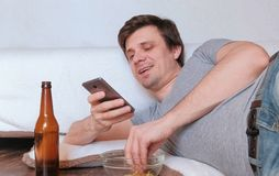 Knappe jonge mensenvrijgezel die spaanders eten en bier drinken en zijn mobiele telefoon doorbladeren stock fotografie