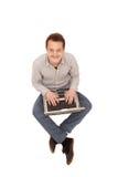 Knappe jonge mensenzitting met computer Royalty-vrije Stock Afbeeldingen