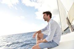 Knappe jonge mensenzitting op varende boot Royalty-vrije Stock Foto