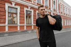 Knappe jonge modieuze modelmens met kapsel in zwarte t-shirt stock afbeeldingen