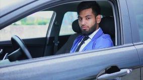 Knappe jonge moslimmensenzitting in de auto en het kijken met het doordringen blik stock footage