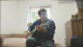 Knappe jonge musicus die de gitaar en het zingen spelen Mens die Akoestische Gitaar dicht omhoog langzame geanimeerde video spele stock video