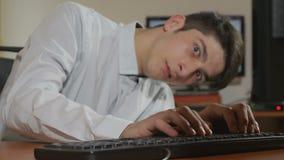 Knappe jonge programmeur die over en de camera buigen onderzoeken stock video