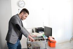 Knappe jonge reparatie die tussen mens en computer een Desktop bevestigen bij klantenhuis Stock Fotografie