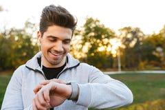 Knappe jonge sportman in openlucht in park het luisteren muziek met oortelefoons die horloge bekijken royalty-vrije stock afbeeldingen