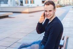 Knappe jonge student die mobiele telefoon met behulp van. Royalty-vrije Stock Afbeeldingen