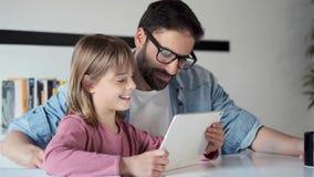 Knappe jonge vader met zijn dochter die zij digitale tablet thuis gebruiken stock footage