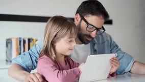 Knappe jonge vader met zijn dochter die zij digitale tablet thuis gebruiken stock video
