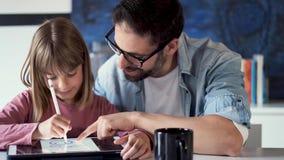 Knappe jonge vader met zijn dochtertekening met digitale tablet thuis stock video