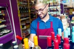 Knappe jonge verkoper die een wijnfles in de winkel van de gezondheidskruidenierswinkel selecteren Royalty-vrije Stock Foto's