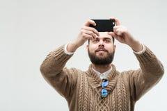 Knappe jonge volwassen nemende foto met zijn smartphone stock fotografie