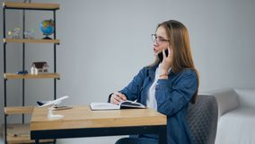 Knappe jonge vrouw die op de smartphone in het reisbureau spreken stock footage