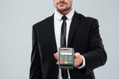 Knappe jonge zakenman die u betalingsterminal geven stock afbeeldingen