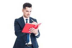 Knappe jonge zakenman het schrijven nota's over een notitieboekje Royalty-vrije Stock Fotografie