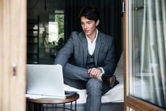 Knappe jonge zakenman in kostuum die aan laptop werken stock afbeelding
