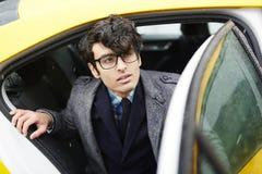 Knappe Jonge Zakenman Leaving Taxi in Regen royalty-vrije stock foto