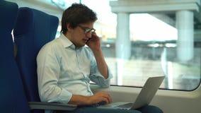 Knappe jonge zakenman op telefoon en het gebruiken van laptop in een trein stock video