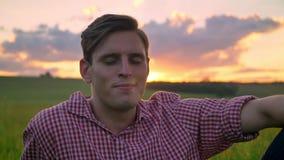 Knappe jonge zekere mensenzitting op tarwegebied die, die en camera, mooie mening met binnen zonsondergang glimlachen bekijken stock videobeelden