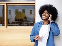 Knappe jonge zwarte mens die mobiele telefoon met behulp van Royalty-vrije Stock Foto