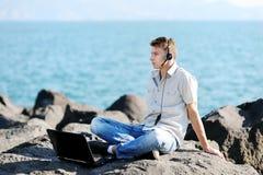 Knappe jongen die aan muziek van zijn laptop luisteren Stock Afbeelding