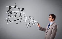 Knappe jongen die en aan muziek met muzieknoten zingen luisteren Stock Foto