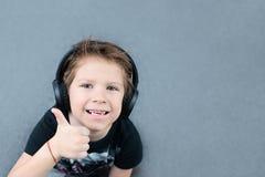 Knappe jongen die in hoofdtelefoons aan muziek luisteren stock foto