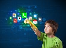 Knappe jongen die kleurrijke mobiele app pictogrammen met bokeh drukken backg royalty-vrije stock fotografie