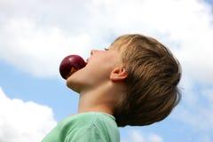 Knappe jongen die pret met een perzik maakt Stock Afbeeldingen