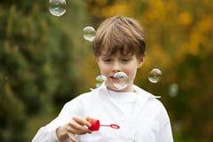 Knappe jongen het letten op zeepbels Stock Foto