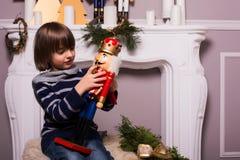 Knappe jongen met stuk speelgoed op Kerstmisachtergrond Stock Fotografie