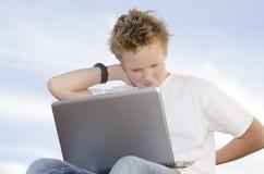 Knappe jongensrust met mobiele computer Stock Foto's