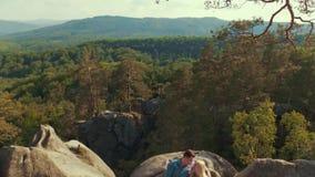 Knappe jongeren in een vrijetijdskleding De aanbiddelijke jonge die minnaars liggen op de bergsteen door bos wordt omringd stock videobeelden