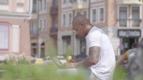 Knappe kale mens die van het Middenoosten met laptop zitting aan de bank in de straat werken Freelance concept E stock videobeelden