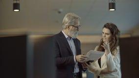 Knappe Kaukasische hogere CEO en zijn leuke vrouwelijke medewerker die een zaken georiënteerde bespreking hebben stock video