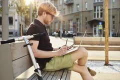 Knappe Kaukasische mens die laptop zitting openlucht in een park gebruiken De dag van de de zomerzonneschijn Concept het jonge be stock afbeelding