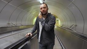 Knappe Kaukasische mens die op roltrap telefoneren stock videobeelden