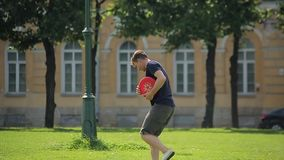 Knappe Kaukasische mens die rode frisbee in openlucht spelen stock video