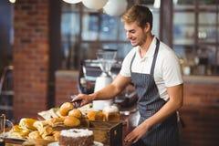 Knappe kelner die een broodje opnemen Stock Foto's