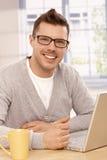 Knappe kerel die laptop het glimlachen gebruikt stock afbeeldingen