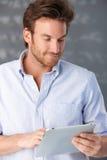 Knappe kerel die touchscreen computer met behulp van Stock Foto